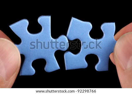 Hands holding two pieces of blue puzzle and fitting them together concept for solution or partnership