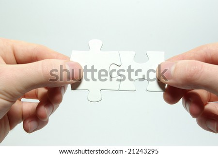 Hands holding two  puzzle for joining
