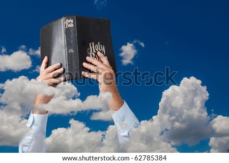 Hands holding up Bible in sky with clouds - stock photo