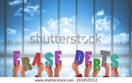 Hands holding up erase debts against room with large window looking on city skyline
