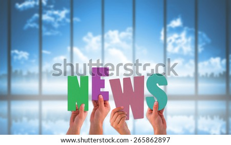 Hands holding up news against room with large window looking on city skyline