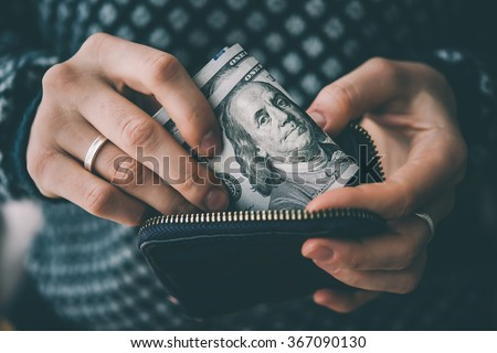 Hands holding us dollar bills and small money pouch. Toned picture