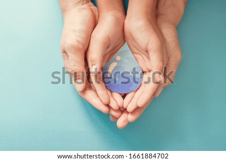 Hands holding water drop, world water day,  clean water and sanitation, hand sanitizer and hygiene for coronavirus pandemic, family washing hands, CSR, save water, clean renewable energy concept