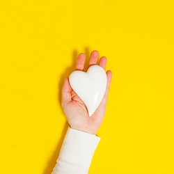 Hands holding white heart over table background. Top view of hand holding white heart isolated on yellow background. Health care, donate, world heart day and world health day concept