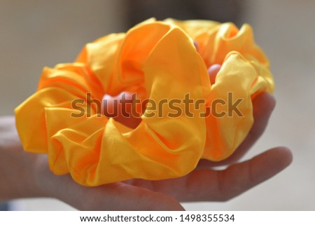 Hands holding yellow and gold hair scrunchy ties for fixing ponytails and other hairstyles