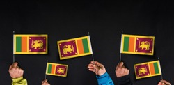 Hands holds flags of Sri Lanka on dark background