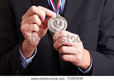 Hands in a business suit holding a silver medal