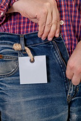 Hands in a red plaid shirt fasten the zipper on the blue jeans. A gray paper label weighs on a sling on a thick rope