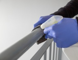 Hands in blue rubber gloves holding microfiber cleaning cloth and spray bottle with sterilizing solution make cleaning and disinfection for good hygiene of a stair railing. Prevention of coronavirus