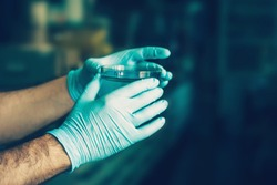 Hands in blue rubber protective gloves holding a Petri dish with a chemical sample in laboratory, with blurred background