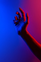 Hands in colorful blue red contrast neon light. Man showing hand palm gesture sign. Vertical orientation photo. Trendy party club style illumination. Space for text. Stylish minimalist background
