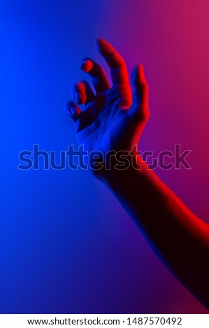 Hands in colorful blue red contrast neon light. Man showing hand palm gesture sign. Vertical orientation photo. Trendy party club style illumination. Space for text. Stylish minimalist background  #1487570492