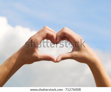hands in form of heart on blue sky background