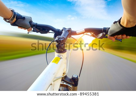 Hands in gloves holding handlebar of a bicycle. Motion blurred asphalt road