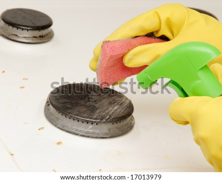 Hands in gloves washing cooking oven with sponge and liquid.