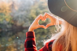 Hands in heart shape. Female hands heart shape on against the background of the autumn forest. I like autumn. blonde girl in a red jacket walks in the autumn on the nature.
