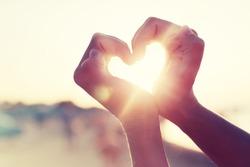 hands in heart shape framing setting sun at sunset on beach