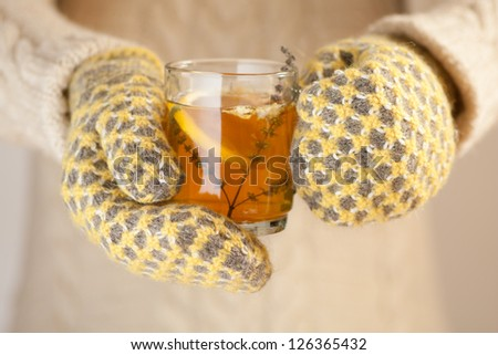 Hands in knitted mittens holding a cup of herbal tea with lemon on a cold day - stock photo