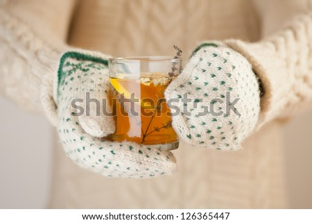 Hands in knitted mittens holding a cup of herbal tea with lemon on a cold day