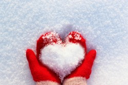 hands in knitted mittens with a heart made of snow on a winter day