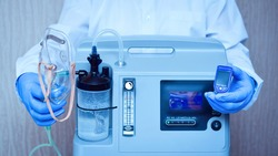Hands in medical gloves hold an oxygen mask from the generator oxygen concentrator, which helps with low lung oxygen saturation, with pneumonia Covid-19 and pulse Oximeter in the other hand