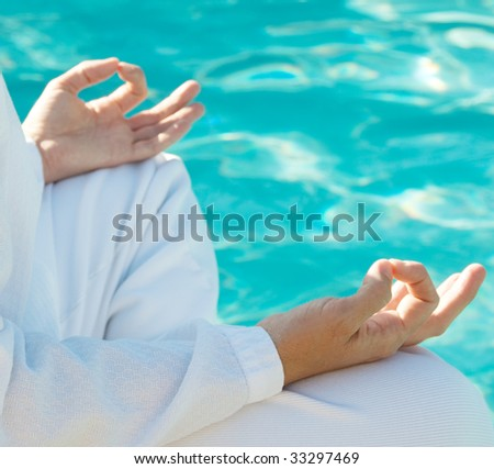 Hands in meditation mudra above water, shallow depth of field, focus on front hand