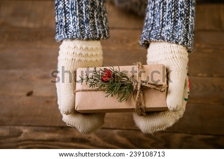 Hands in mittens holding gift box. Woman holding modern Christmas present gift