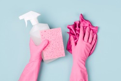 Hands in pink gloves hold detergents. Cleaning or housekeeping concept background. Copy space. Flat lay, Top view.