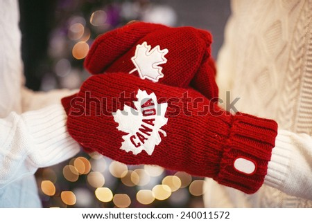 Hands in red gloves over the Christmas tree with Canada sign