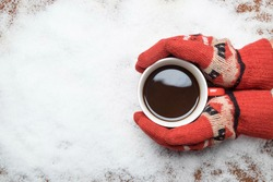 Hands in red teal gloves holding a coffee mug on snow.