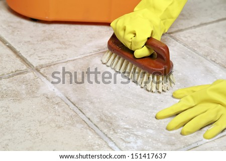 hands in rubber gloves scrubbing the floor