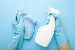 Hands in rubber protective gloves holding white spray bottle and rag. Detergent for different surfaces in kitchen, bathroom and other rooms. Closeup. Light pastel blue background. Point of view shot.