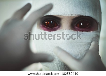 Hands in surgical gloves are drawn to face, close-up portrait