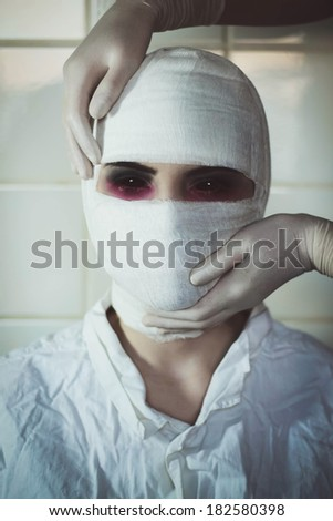 Hands in surgical gloves is holding bandaged head