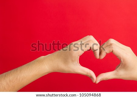 Hands in the shape of heart isolated on red background