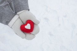 hands in white knitted gloves hold a red heart - a symbol of love and happiness, February 14 Valentine's Day