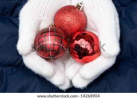 hands in white mittens hold 3 red christmas balls - stock photo