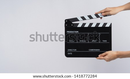 Photo of  Hands is holding black Clapperboard or movie slate. it use in video production ,film, cinema industry on white background.