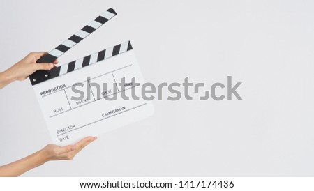 Photo of  Hands is holding Clapperboard or movie slate. it use in video production ,film, cinema industry on white background.