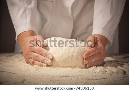 hands kneading bread dough
