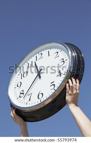Hands lifting big clock outdoors - stock photo