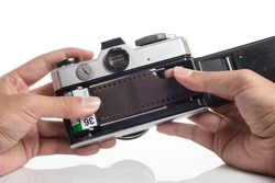 Hands loading film into SLR camera