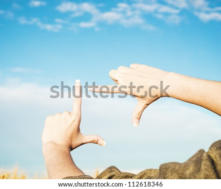 Hands making a frame in the sky