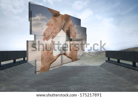 Hands making a house on abstract screen against road leading out to the horizon
