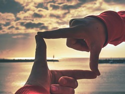 Hands making finger shape gesture, hand hold sun above stony fisherman pier, Mallorka island.