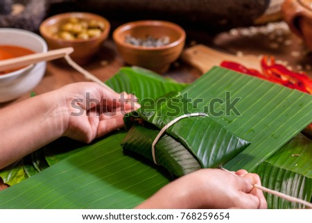 Hands making Guatemalan tamales.