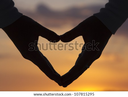Hands making heart at beautiful sunset-symbol of love - stock photo