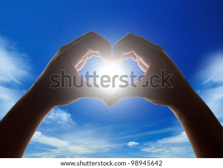 Hands making heart shape with sun in center and cloudy blue sky in background