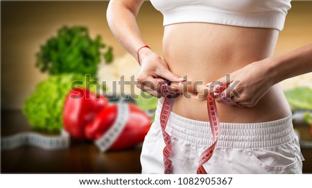 Hands measuring waist with a tape #1082905367