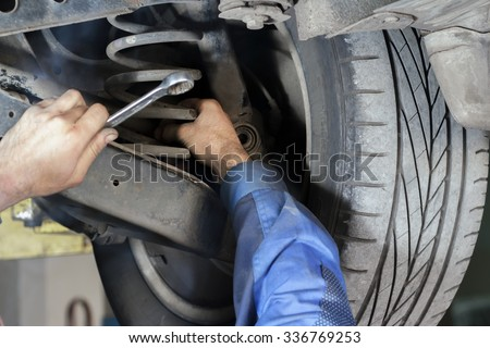 Hands mechanics to repair the suspension on the car #336769253